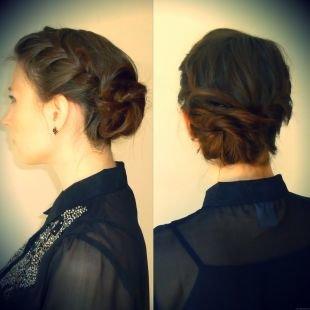 Темно каштановый цвет волос, прическа с плетением вокруг головы и низким пучком
