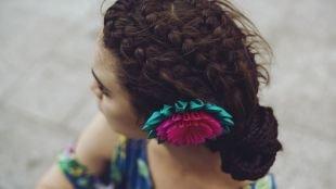 Цвет волос темный каштан, прическа низкий пучок с несколькими косами и цветком